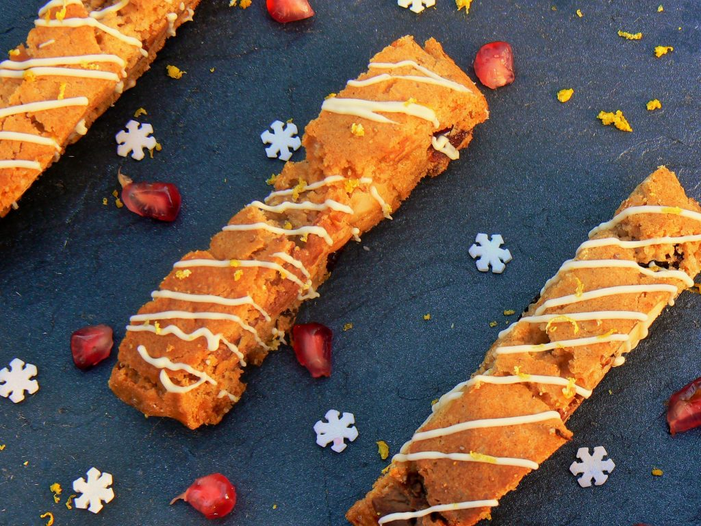 My Vegan Christmas Cake Biscotti Recipe, can be made in advance and kept in pretty cellophane bags ready to hand out (also makes lovely goodie bags!)  These have all the flavours of Christmas Cake in a yummy, dunkable biscotti filled with cranberries, dark chocolate chunks and brazil nuts then topped with white chocolate drizzle and grated lemon zest!