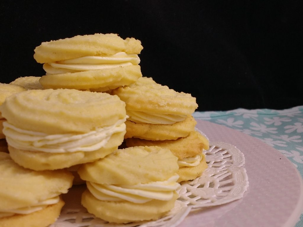 These Glutenfree Almond & Vanilla Viennese Whirls are so easy to make but look absolutely beautiful. No style over substance here though as they are simply delicious & melt in the mouth! These are filled with a dairyfree vanilla buttercream and a large splodge of raspberry jam but you can use just about any flavour combination you like!