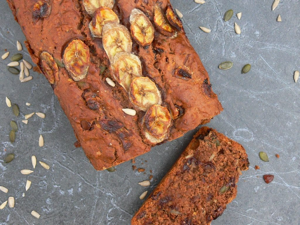 Vegan Chocolate Banana Bread, a delicious, nutritious lunchbox staple in this house. Full of crunchy seeds, soft dried fruits and chunks of dark chocolate. This quick & easy one bowl recipe keeps well in an airtight tin and can be frozen in slices. Dairy Free, Nut Free and can be made Gluten Free by using a suitable flour.